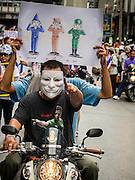 """14 JULY 2013 - BANGKOK, THAILAND:  Anti-government protesters ride a motorcycle through central Bangkok Sunday. About 150 members of the so called """"White Mask"""" movement marched through the central shopping district of Bangkok Sunday to call for the resignation of Yingluck Shinawatra, the Prime Minister of Thailand. The White Mask protesters are strong supporters of the Thai monarchy. They claim that Yingluck is acting as a puppet for her brother, former Prime Minister Thaksin Shinawatra, who was deposed by a military coup in 2006 and now lives in exile in Dubai.       PHOTO BY JACK KURTZ"""