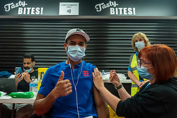 """© Licensed to London News Pictures. 27/06/2021. WATFORD, UK. Rafael Nunezl (aged 36) receives a first dose of the Pfizer vaccine at a pop-up mass vaccination clinic at Watford FC's Vicarage Road Stadium as part of the """"Grab a jab"""" campaign. The NHS is also promoting a number of walk-in clinics this weekend across the capital to try to increase the number of over 18s receiving a jab as cases of the Delta variant are reported to be on the rise..  Photo credit: Stephen Chung/LNP"""
