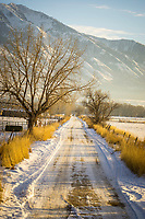 A small town country road in Utah leads off into the fields at sunset in Winter.