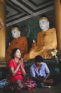 Yangon, Myanmar - November 15, 2011: A Burmese couple visits the Shwedagon Pagoda in central Yangon. The man looks at his phone while the woman prays.