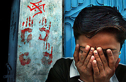 Nisha Rathad, 20, covers her face and giggles as she stands in front of the Hindu Aryan symbol painted on her home March 2, 2002 in Ahmedabad, India. Her Muslim neighbor had been killed a few feet away from her home the day before. These symbols were painted on most Hindus homes to protect them from the religious violence that swept through this region and killed over three hundred people in three days, the worst communal bloodshed in a decade.