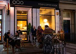 Night view of people sitting outside small  OQO cafe on Leith Walk, Edinburgh, Scotland, UK