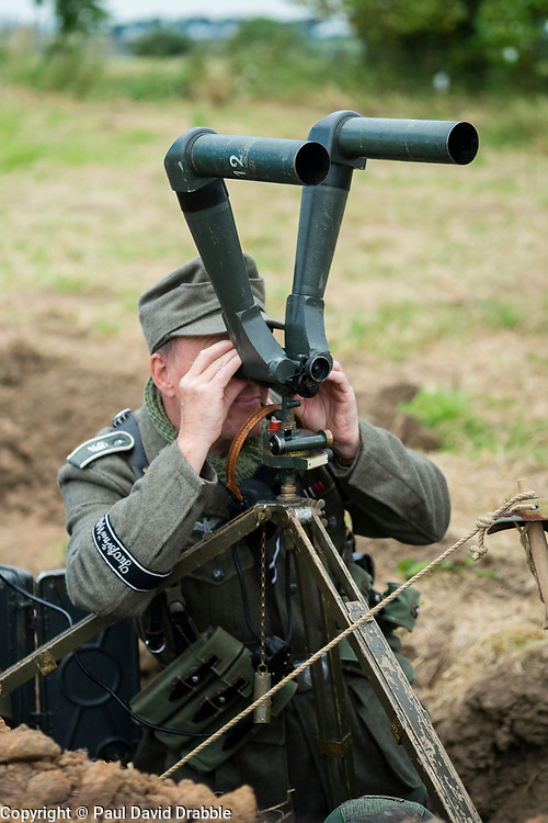 A reenactor portraying a member of the Panzer-Grenadier-Division Großdeutschland  stands in a dug out observation  trench looking through a pair of donkey Ears' Trench Binoculars which are mounted on a wooden tripod. at  Ackworth Steam Rally  17 July 2016<br />  Copyright Paul David Drabble<br />  www.pauldaviddrabble.photoshelter.com