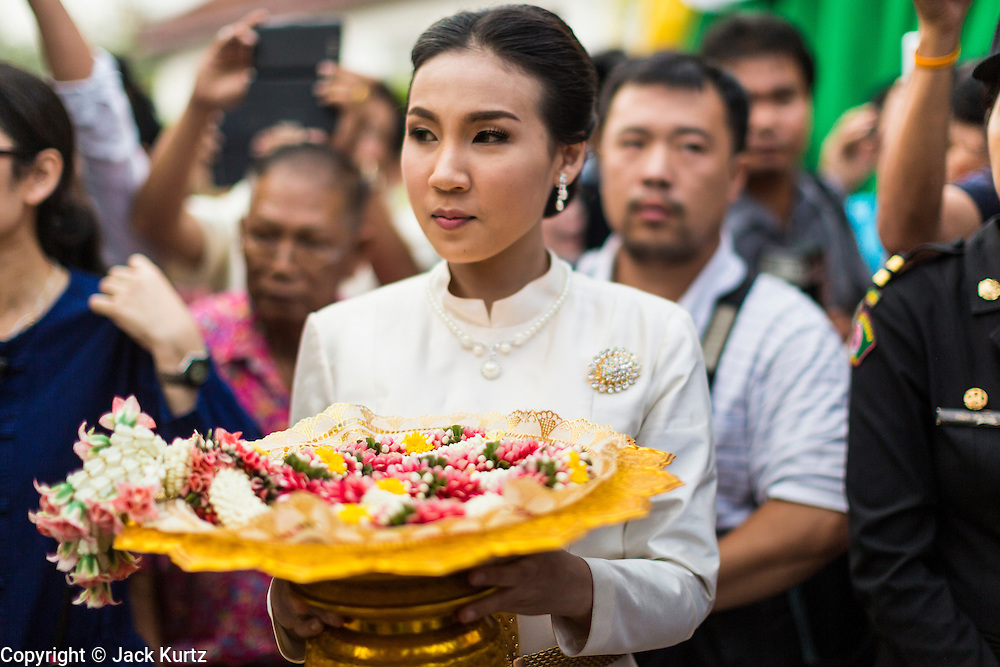 12 APRIL 2014 - BANGKOK, THAILAND:  A woman holds flower garlands for offering to the Phra Buddha Sihing at the National Museum. The Phra Buddha Sihing, a revered statue of the Buddha, is carried by truck through the streets of Bangkok so people can make offerings and bathe it in scented oils. Songkran is celebrated in Thailand as the traditional New Year's from 13 to 16 April. The date of the festival was originally set by astrological calculation, but it is now fixed. The traditional Thai New Year has been a national holiday since 1940, when Thailand moved the first day of the year to January 1. The first day of the holiday period is generally the most devout and many people go to temples to make merit and offer prayers for the new year.   PHOTO BY JACK KURTZ