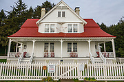 The Keepers' House, at Heceta Head Lighthouse State Scenic Viewpoint, 14 miles south of Yachats on the Oregon coast, USA. Since 1995, the Keepers' House has been operated by the Heceta Lighthouse Bed & Breakfast, a concessionaire of the U.S. Forest Service. Built in 1893, the Heceta Head Light and Keepers Quarters were placed on the National Register of Historic Places in 1978 for architectural and engineering significance. The site originally included farm buildings and the single-family head lighthouse keeper's house, which was demolished in 1940 and had been similar to the remaining house shown here. Due to electrification, the head lighthouse keeper was no longer needed, and the original house was sold for $10, dismantled for its lumber, and used to build Alpha Bit bookstore-cafe in Mapleton, still standing today. The remaining keepers' house was a duplex that housed the first and second assistant lighthouse keepers and their families. After the beacon was automated in 1963, the last keepers moved away. From 1970 to 1995, the U.S. Forest Service leased the Keepers' House to Lane Community College for use as a satellite campus. The porch of the Queen Anne-style house was restored in 1981.