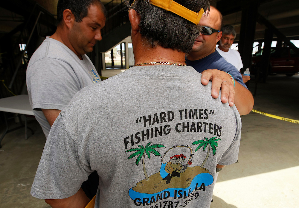 Charter boat captains waiting for economic loss checks from BP talk in Grand Isle, Louisiana May 12, 2010. Left to right are: Joel Bradberry, Mark Scardino and Pete Besson. The three all said they had lost most of their scheduled trips so far this season due to the oil spill. REUTERS/Rick Wilking (UNITED STATES)
