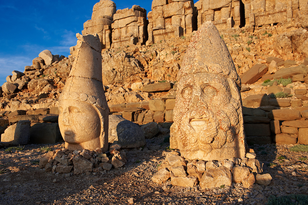 Pictures & Images of the statues of around the tomb of Commagene King Antochus 1 on the top of Mount Nemrut, Turkey. Stock photos & Photo art prints. In 62 BC, King Antiochus I Theos of Commagene built on the mountain top a tomb-sanctuary flanked by huge statues (8–9 m/26–30 ft high) of himself, two lions, two eagles and various Greek, Armenian, and Iranian gods. The photos show the broken statues on the  2,134m (7,001ft)  mountain. 3
