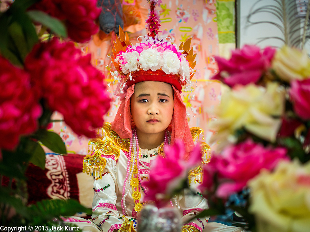 """04 APRIL 2015 - CHIANG MAI, CHIANG MAI, THAILAND:  A Tai boy sits in an alter in his family's living space at Wat Pa Pao during the Poi Sang Long Festival. Friends and family will visit him and pray with him before the ordination ceremony. The Poi Sang Long Festival (also called Poy Sang Long) is an ordination ceremony for Tai (also and commonly called Shan, though they prefer Tai) boys in the Shan State of Myanmar (Burma) and in Shan communities in western Thailand. Most Tai boys go into the monastery as novice monks at some point between the ages of seven and fourteen. This year seven boys were ordained at the Poi Sang Long ceremony at Wat Pa Pao in Chiang Mai. Poy Song Long is Tai (Shan) for """"Festival of the Jewel (or Crystal) Sons.     PHOTO BY JACK KURTZ"""