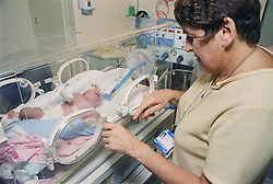 Family Care Sister comforting baby on Neonatal unit being ventilated in an incubator,