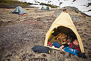 Backpacker Charlie Bloch lies in his tent sleeping, snuggling with his dog, at camp above Parika Lake, Never Summer Wilderness, Colorado.