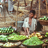 A youngster vends his fruits and vegetbles in a bazaar in Dhaka, Bangladesh.
