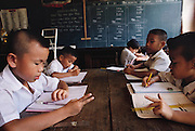 Nine-year-old Visith Khuenkaew, left, and his fellow third grade classmates work on math problems at school near their village of Ban Muang Wa, Thailand. Published in Material World, page 84. The Khuenkaew family lives in a wooden 728-square-foot house on stilts, surrounded by rice fields in the Ban Muang Wa village, outside the northern town of Chiang Mai, in Thailand.