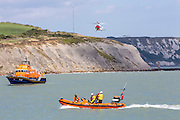 The Royal National Lifeboat Institution RNLI Dover Life boat (17-09),  HM Coastguard rescue helicopter (G-C1JW)  and the Dymchurch based RNLI Inshore lifeboat - (B-766) take part in a joint training exercise in front of the white cliffs outside Folkestone Harbour, Folkestone, Kent. UK. 6th August 2016 (photo by Andrew Aitchison / In pictures via Getty Images)