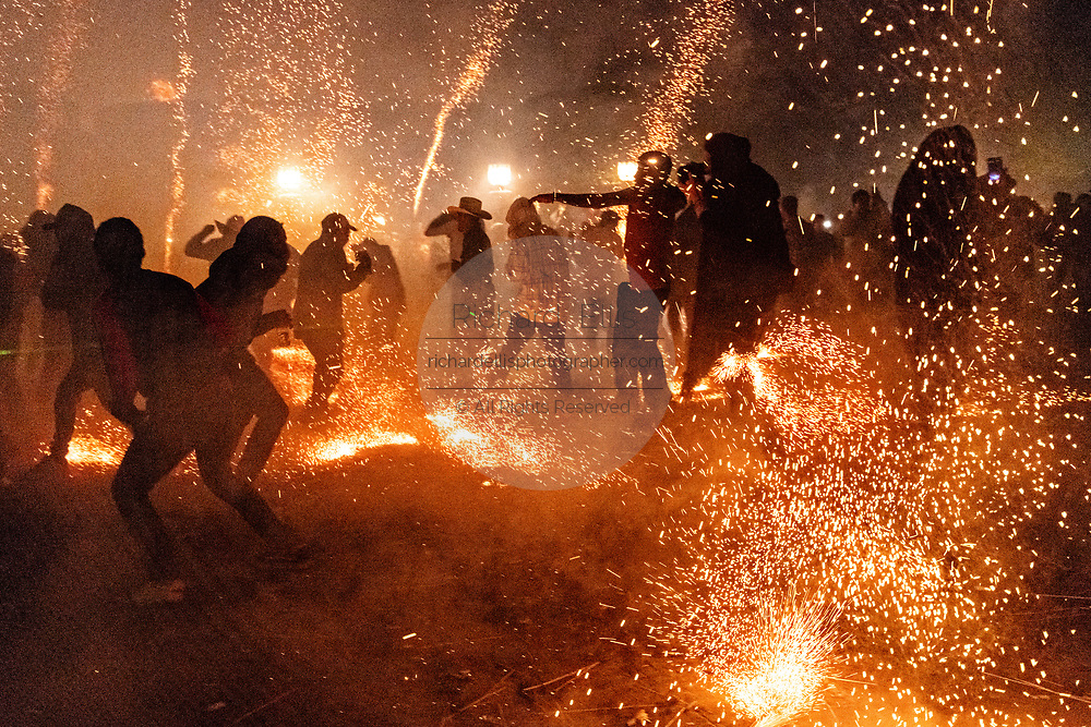 Sparks from exploding sky rockets scatter as Mexicans run for cover during a barrage of pyrotechnic rockets during the Alborada festival September 29, 2018 in San Miguel de Allende, Mexico. The unusual festival celebrates the cities patron saint with a two hour-long firework battle at 4am representing the struggle between Saint Michael and Lucifer.