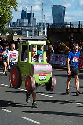 © Licensed to London News Pictures. 03/10/2021. LONDON, UK. A runner in a tractor costume on Embankment passes mile 25 in the London Marathon, the first time it has been held since April 2019 due to the Covid-19 pandemic.  Over 36,000 elite athletes, club runners and fun runners are taking part in the mass event, with another 40,000 people taking part virtually.  Photo credit: Stephen Chung/LNP