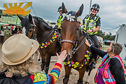 Police horses (one of which has Glastonbury stencilled on his bridle) with floral garlands are popular with the crowds - The 2017 Glastonbury Festival, Worthy Farm. Glastonbury, 23 June 2017