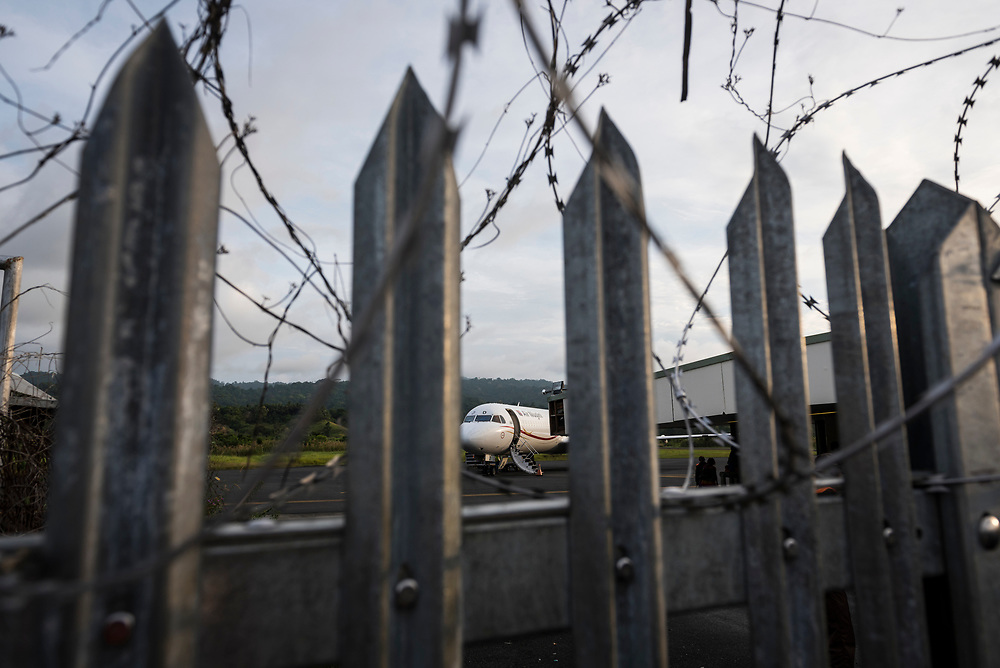 An Air Niugini Fokker 100 plane, viewed through a fence topped with razor wire, is parked at Wewak airport in Papua New Guinea. (July 21, 2017)