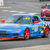 Kerry Wade (11) in the LF Performance / The Rotary Shop Mazda RX7 leads Graham Stones (3) in his Rotomotion / Stones Motorsport Mazda RX7 into Turn 1 at Wanneroo Raceway.