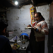 Deepa Bhatt, a member of the women's knitting circle, eats lunch with her husband in their home on the outskirts of Ranikhet, India on Dec. 4, 2018.