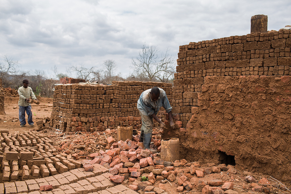 Near Chipanga, Tete province, Mozambique. Workers in a brick manufacture. Because there are no job opportunities in the resettlements and around these workers returned to their old brick manufactrure (40 km away) and stay here for the week and only return to their families on the weekends...Over 700 families from the villages of Chipanga, Mitete, Malabue-Gombe and Bagamoyo were resettled to Cateme village, a Vale resettlement compound. Vale deliberately divided the communities in two with employed villagers moving to 25 de Setembro since it is closer to Moatize and the coal mine. The unemployed were resettled to Cateme, 40 km from the original town. While the most immediate problem of the community is the enormous distance to Moatize, their old habitat, they also suffer from unproductive farmland which can only be reached via a two hour walk, no access to markets and infrastructure and poorly constructed houses not fitted to the people's needs with temperatures inside reaching as high as 65° C due to the construction with tin clad roofs and missing isolation.