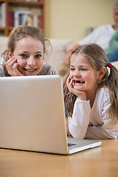 Granddaughters looking in laptop while grandparents in background