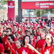"© Maria Muina I MAPFRE. MAPFRE fans and students from the Crescer high school of Itajaí walking from the MAPFRE office to the Race Village to support the team with a red flag named Torcida do MAPFRE. / Fans y estudiantes del colegio Crescer de Itajaí realizan una marcha desde la sucursal de MAPFRE al Race Village para apoyar al equipo con una bandera gigante con el lema ""Torcida do MAPFRE""."