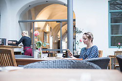 Young woman using mobile phone at restaurant
