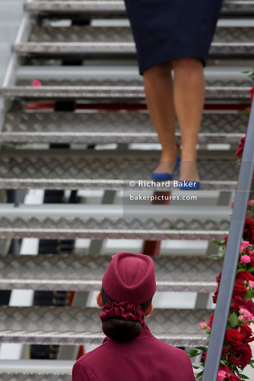 Cabin crew hostess at the bottom of steps a Qatar Airways Boeing 787 at the Farnborough Air Show, UK.