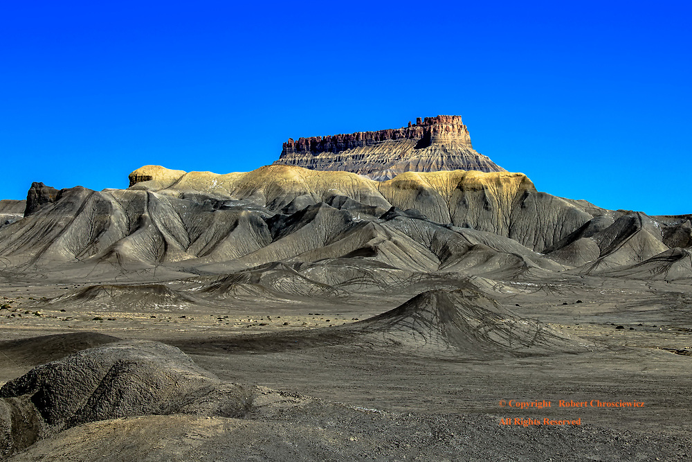 Factory Butte: The monumental feature known as Factory Butte is seen to overlook the arid barren hills and sand dunes near Coal Mine Wash, Utah USA.