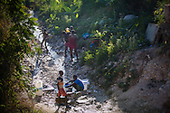 Haitians use  a creak to get their water and bathe in Cabaret, a small town north of Port-au-Prince, Haiti. The lack of clean water and sanitation has made Haiti ripe for the spread of cholera, an epidemic that claimed over 2000 lives in the first two months.