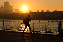 © Licensed to London News Pictures. 20/01/2017. LONDON, UK.  A man walks along the Thames path during hazy sunrise seen over the River Thames. London is continuing to experience cold weather and has received pollution warnings again this morning. Photo credit: Vickie Flores/LNP