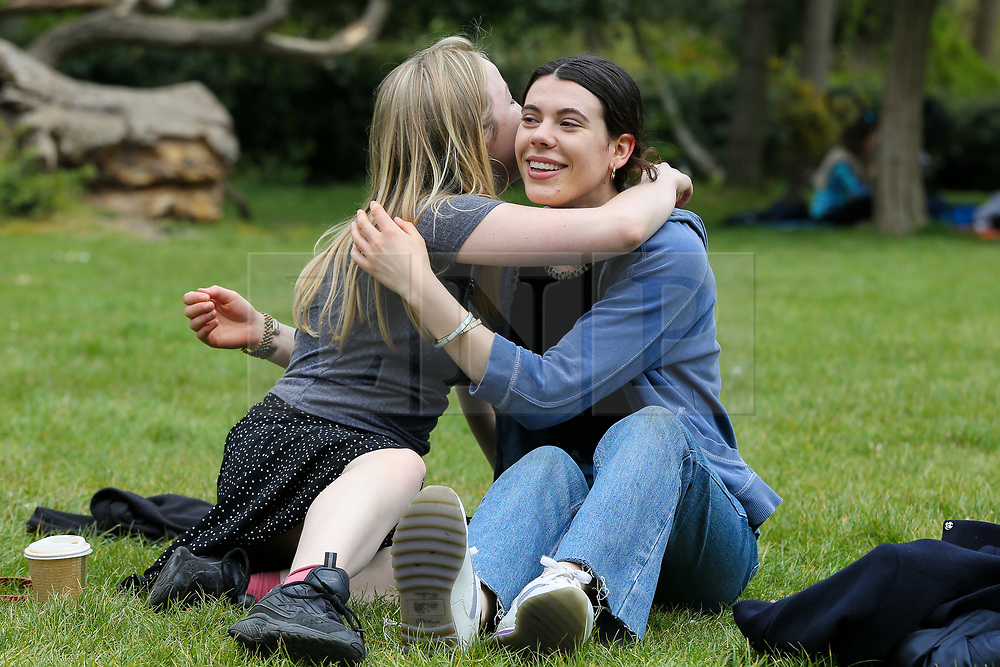 © Licensed to London News Pictures. 09/05/2021. London, UK. Two friends in the same bubble hug each other in Finsbury Park, north London on a warm day. On Monday 10 May, Prime Minister Boris Johnson will announce that family and friends in England will be allowed to hug each other again from 17 May 2021. <br /> <br /> *** Permission Granted *** <br /> <br /> Photo credit: Dinendra Haria/LNP