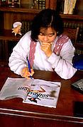 Korean woman age 29 filling out magazine quiz on self esteem.  St Paul Minnesota USA