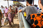 """17 JUNE 2013 - YANGON, MYANMAR:  Passengers get off in Dala (on the left) and line up to get to go Yangon on (on the right) the Dala-Yangon Ferry across the Yangon River. The ferry to Dala opposite Yangon on the Yangon River is the main form of transportation across the river. Every day the ferry moves tens of thousands of people across the river. Many working class Burmese live in Dala and work in Yangon. The ferry is also popular with tourists who want to experience the """"real"""" Myanmar. The rides takes about 15 minutes. Burmese pay about the equivalent of .06¢ US for a ticket.  Foreigners pay about the equivalent of about $4.50 US for the same ticket.    PHOTO BY JACK KURTZ"""