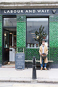Tom, a shop assistant outside the fashionable hardware shop, Labour and Wait, London, UK<br /> Labour and Wait sell new and vintage industrial and utility homewares to a fashionable customer base.