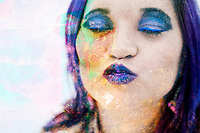 Woman with purple hair her lips puckered in a kiss.