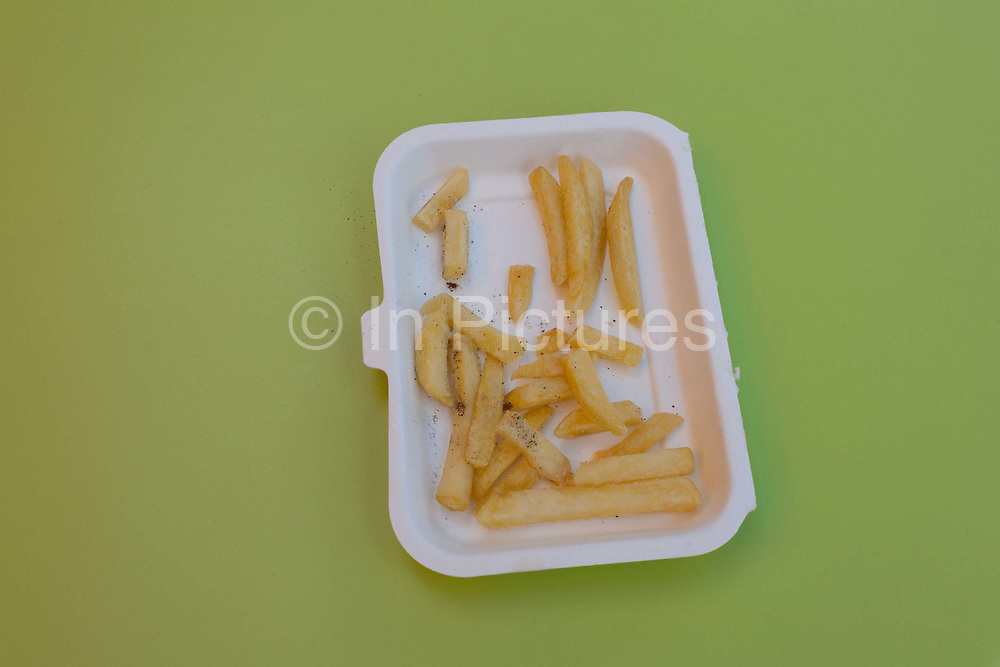 A detail of half-eaten chips fries left in a styrofoam dish, on a green cafe table in central London, on 6th October 2016, in London, England.