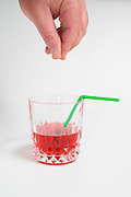 Conceptual image of a male hand adding Date rape drug (GHB gamma-hydroxybutyric acid) to a cocktail. These drugs can be used to assist in the commission of a sexual assault