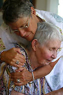 A woman with Alzheimer's disease is hugged by a healthcare worker  at  live-in residence for Alzheimer's and dementia related  patients.