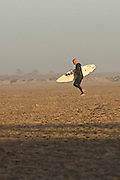 A surfer walks back from the water in St Augustine Beach, Florida.