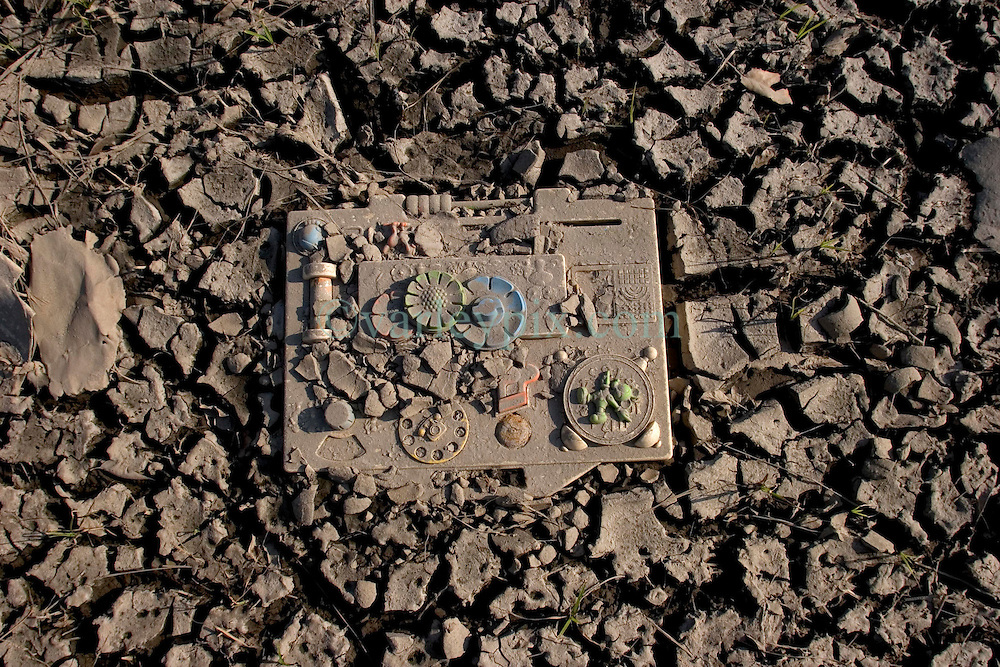 30 Sept, 2005.  New Orleans, Louisiana. Lower 9th ward. Hurricane Katrina aftermath. <br /> The remnants of the lives of ordinary folks, now covered in mud as the flood waters remain. A baby's toy and early learning device lays in the mud.<br /> Photo; ©Charlie Varley/varleypix.com