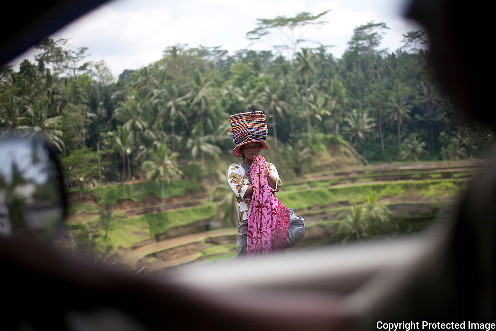 A woman selling sarangs stands on the side of a road waiting for tourists near Ubud Bali,Indonesia.