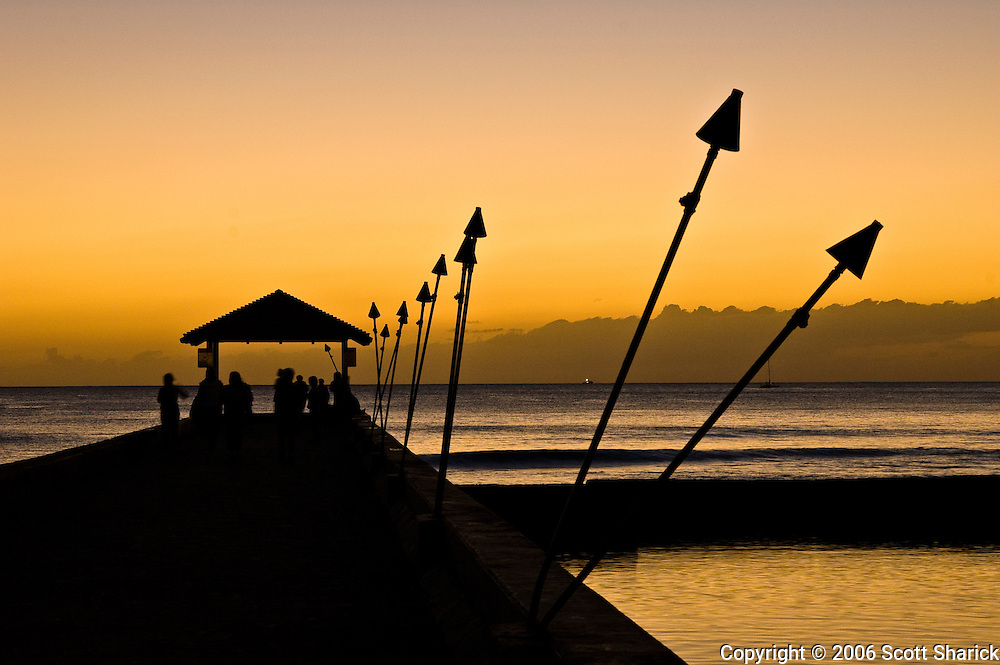 Sunset at the Kapahulu Groin in Waikiki showing unlit torches in silhouette.