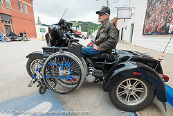 John Lean of Reynolds, ND parked just off Main Street with his Harley-Davidson Tri-Glide, which he modified to carry his wheel chair during the annual Sturgis Black Hills Motorcycle Rally. Sturgis, SD, USA. August 6, 2014.  Photography ©2014 Michael Lichter.