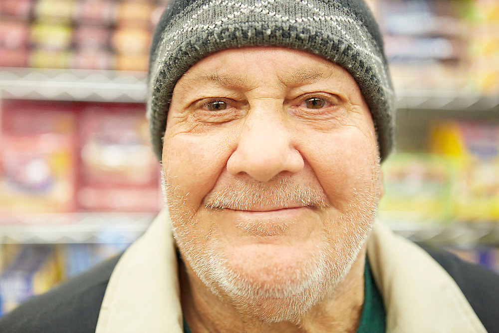 Close up portrait photograph of white beard senior man wearing hat inside grocery store