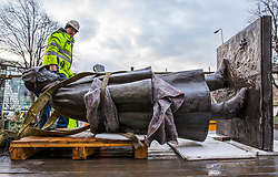 The sculpture of Sherlock Holmes by former pop-artist Gerald Laing is being moved from it's home on Picardy Place, yards from the birth place of Sir Arthur Conan Doyle.<br /> <br /> The move of the sculpture is to accommodate road and tram works that are taking place in Edinburgh. The statue will be moved to Nairn at  Black Isle Bronze Ltd by the artists son, Farquhar Laing where it will stay for two years until it returns to Edinburgh.<br /> <br /> Pictured: One of the lifting team checks over the statue as it lays on the truck that will take it for restoration in Nairn