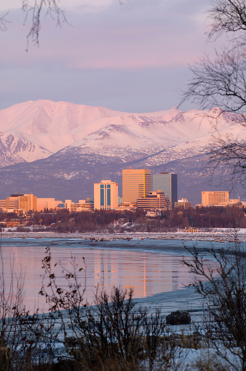 Alaska.  City of Anchorage with the cityscape reflection in waters of Cook Inlet as seen from Earthquake Park in winter.
