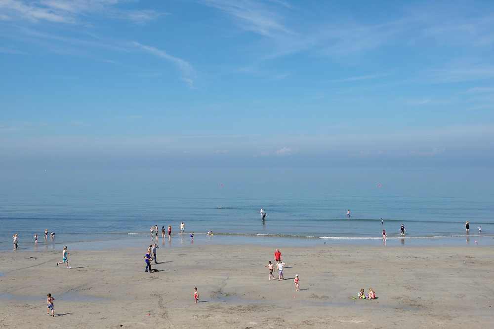 People enjoy a June afternoon at the beach in Ballygally, Northern Ireland