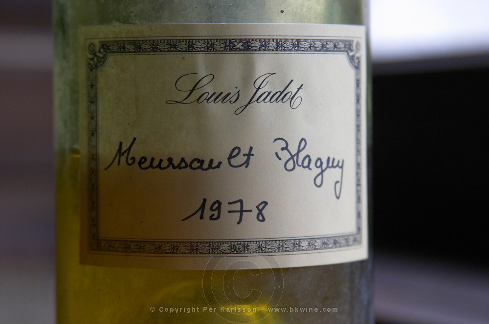 A half empty dusty old bottle in side light with a hand written label saying Louis Jadot Meursault Blagny 1978 white burgundy, Maison Louis Jadot, Beaune Côte Cote d Or Bourgogne Burgundy Burgundian France French Europe European