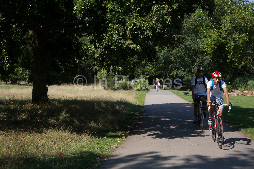 """Friends out cycling. Hampstead Heath (locally known as """"the Heath"""") is a large, ancient London park, covering 320 hectares (790acres). This grassy public space is one of the highest points in London, running from Hampstead to Highgate. The Heath is rambling and hilly, embracing ponds, recent and ancient woodlands."""